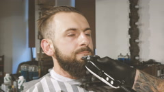 Getting perfect shape. Close-up side view of young bearded man getting beard Stock Footage