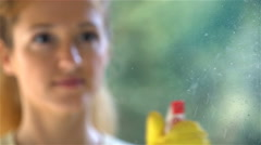 Young attractive woman cleaning a window with a special detergent spray. - stock footage