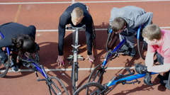 4K Disabled athletes in wheelchairs huddle for team talk at race track Stock Footage
