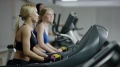 two young blond women walking on treadmill - stock footage