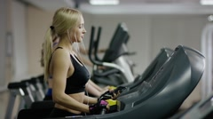 young woman walking on treadmill with white headphones - stock footage