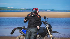 Biker on the bank of the river, next to his motorcycle, makes the photo on the Stock Footage
