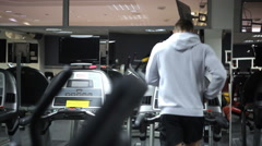 Man in sportswear is engaged on a treadmill in gym Stock Footage