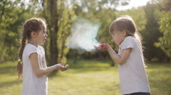 Girls blow away on each other the colours of Holi the festival of colors Stock Footage