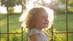 Happy little girl laughing setting sun. Curly girl in sunset light Stock Footage