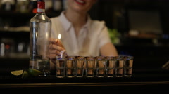 4K Portrait of smiling bartenders standing behind a row of flaming shots - stock footage