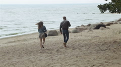 Young couple walking along a sandy beach Stock Footage