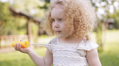 little girl blowing soap bubbles in summer park. - stock footage