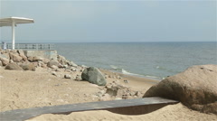 Sea near the shore with a path to the stone columns on land at the water Stock Footage