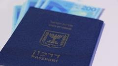 Stack of israeli money bills of 200 shekel and israeli passport - Pan left - stock footage