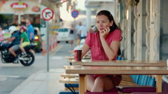 Attractive young womanl with cup, outdoor restaurant. Stock Footage