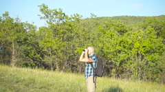 Man tourist looks in binocular in outdoor place in nature. Stock Footage