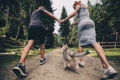 couple runs on road in the nature with dog - stock photo