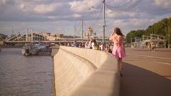 Beautiful brunette girl in pink dress walks along Moscow river embankment. Slow - stock footage