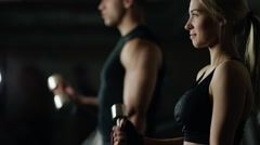 young woman and man doing a fitness workout with dumbbells - stock footage
