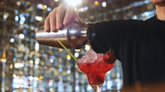 The barman prepares alcoholic cocktail with strawberry - stock footage