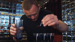 Bartender preparing and lining shot glasses for alcoholic drinks on bar Stock Footage