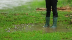 Child In Rubber Boots Standing In Puddle Stock Footage