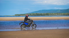 Extreme motorcyclist rides on sandy bank of the river Stock Footage