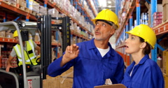 Warehouse worker showing something to colleague Stock Footage