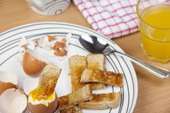 Dipped egg soldier on a plate with a glass of orange Stock Photos