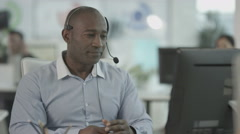 4K Friendly customer service operator talking to customer in busy call centre Stock Footage