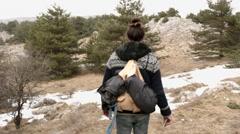Man walk through pines on mountain Stock Footage