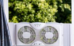 Window fan ready to cool down room in home during hot weather Stock Photos