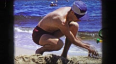 1955: Dad son sand castle ocean beach quality playtime together. - stock footage