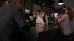 4K Friendly bar staff serving young fun crowd in fashionable city bar. Stock Footage