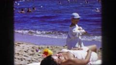 1955: Mother son enjoying beach waves suntanning ocean resting vacation. - stock footage