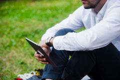Businessman Using Tablet Computer in park. Close-up shot Stock Photos
