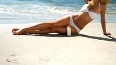 Young woman with sunscreen lotion on beach Stock Footage