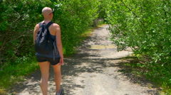 4K Fit Woman Hiking Down Path, Cancer Chemotherapy Survivor Stock Footage