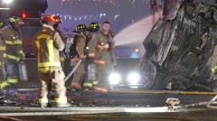 Fire fighters putting water on wreckage after car crash Stock Footage