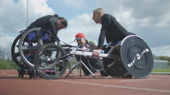 4K Young female wheelchair racer training with coaches at racing track Stock Footage