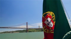 Portuguese flag on a ship on background of 25th April bridge and Jesus statue Stock Footage