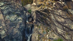 Left to right pan aerial view of waterfall with mountains with color Stock Footage