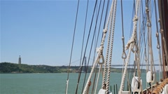 rigging of sailing ship on background of bridge and statue of Jesus - stock footage