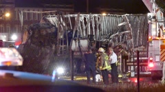 Firemen next to crash with car embedded in truck Stock Footage
