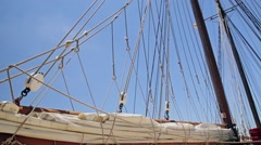 Folded sail and rigging of a sailboat against the sky - stock footage