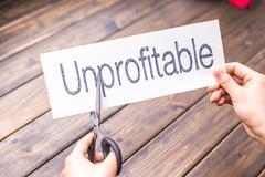 Unprofitable to profitable by scissors Stock Photos