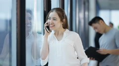 4K Businesswoman standing next to window & talking on cell phone in city office Stock Footage