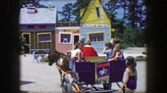 1955: Storyland theme park horse drawn carriage pulling cart of kids amusement Stock Footage