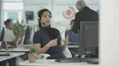 4K Customer service ops taking calls in busy call center with manager overseeing Stock Footage