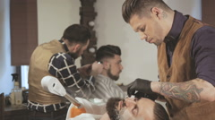 Shaving process of beards in Barbershop. Master makes a haircut beard client - stock footage