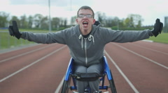 4K Portrait of young disabled athlete in racing wheelchair at sports track Stock Footage