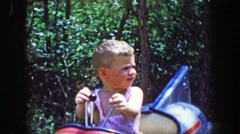 1955: Storyland theme park boy riding rocket amusement toddler kid ride. Stock Footage