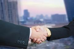 Business handshake with blur background of business buildings area and office - stock photo