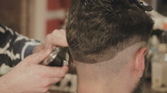 men's hairstyling and haircutting with hair clipper in a barber shop or hair - stock footage